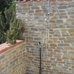 realizzazione doccia esterna con rivestimento in mattoni e pietre